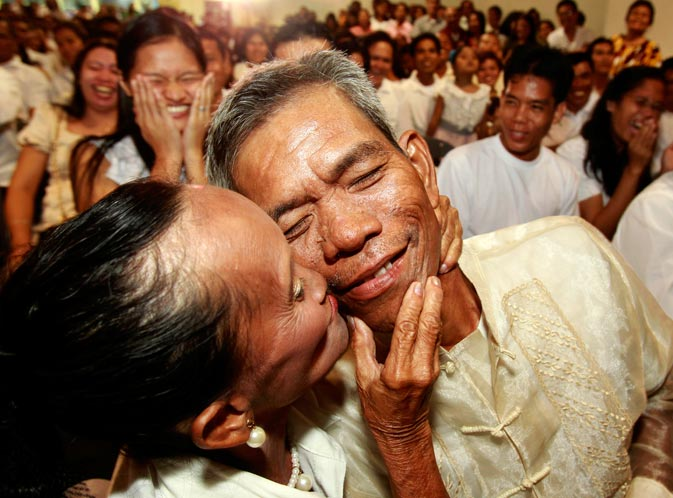 Newly married couple Nonilon and Concepcion Elizalde kiss following a mass wedding sponsored by the city of Paranaque, south of Manila, Philippines on Valentine's Day. More than 300 couples, all residents of the city, tied the knot Tuesday that becomes the annual tradition of the city on Valentine's Day. – AP Photo.