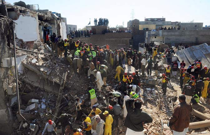 Pakistani security personnel and volunteers search for victims in the rubble of a collapsed factory in Lahore on February 6, 2012. ? AFP Photo