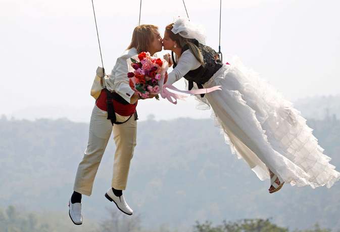 "Thai-Swedish couple William Timhede, 23, left, and Napatsawan Timhede, 39, kiss as they hang on sling wire in a show known as a ""flying wedding"" as part of an adventure-themed wedding ceremony in Prachinburi province, Thailand, on the eve of Valentine's Day. – AP Photo."