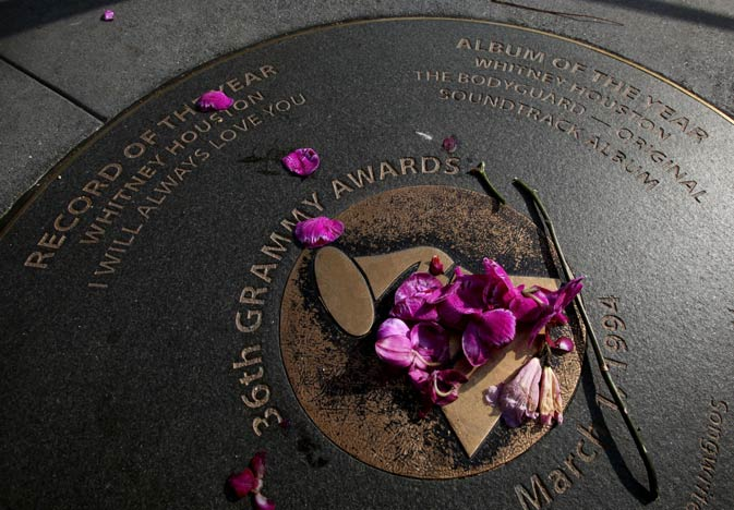 Flowers placed on a Grammy sidewalk plaque honoring Whitney Houston's wins for Record of the Year and Album of the Year in 36th Grammy Awards, have been scattered and replaced several times outside the Grammy Museum in Los Angeles. Houston died Saturday, Feb. 11, 2012, on the eve of the 54th Grammys, at the Beverly Hilton Hotel, where she was preparing to attend a pre-Grammy party. She was 48. ? AP Photo