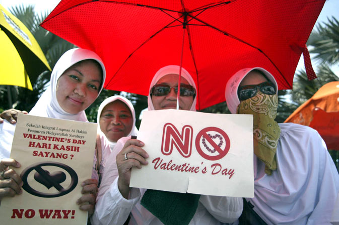 Indonesian female students from a local Islamic boarding school hold up anti-Valentine's Day placards during a protest in Surabaya, East Java province. Conservative Indonesian Islamic groups denounced Valentine's Day, saying it is un-Islamic, promoting promiscuity, casual sex and consumption of alcohol while other groups described the day as foreign cultural influence. – AFP Photo.