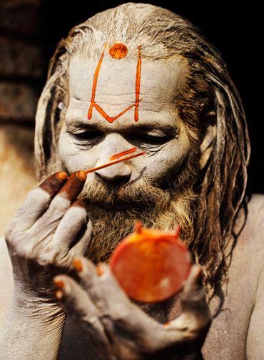 A Hindu holy man, or sadhu, applies paint on his forehead at Pashupatinath Temple in Kathmandu February 14, 2012. Hindu holy men from Nepal and India come to this temple to take part in the Shivaratri festival which falls on February 20. This is one of the biggest Hindu festivals dedicated to Lord Shiva and is celebrated by devotees all over the world, with holy men smoking marijuana and some smearing their bodies with ashes and praying. ? Reuters Photo