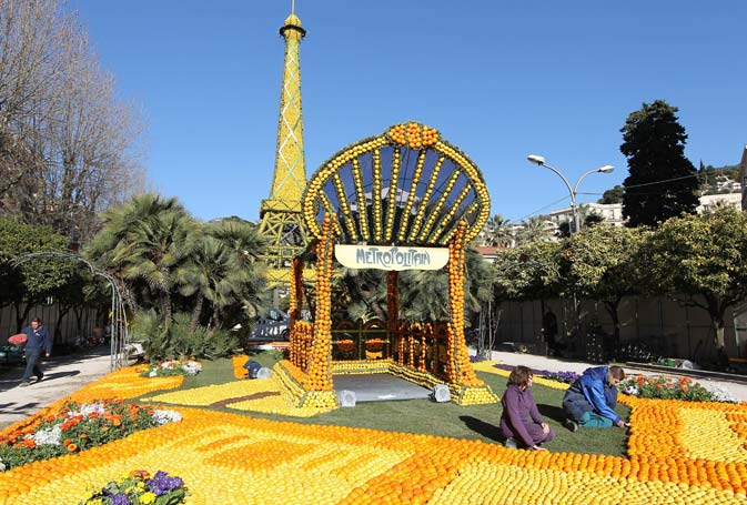 "People work on sculptures made with oranges and lemons representing the Eiffel tower and the entrance of a metro station on February 16, 2012 in Menton on the French Riviera, ahead of the start of the ""Fete du Citron"" (lemon carnival). ? AFP Photo"