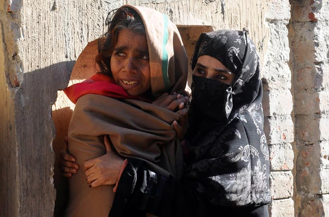 Pakistani women wait for their trapped relatives following a collapsed factory in Lahore on February 6, 2012. ? AFP Photo
