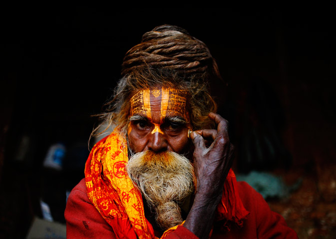 A Hindu holy man, or sadhu, applies paint on his forehead at Pashupatinath Temple. ? Reuters Photo