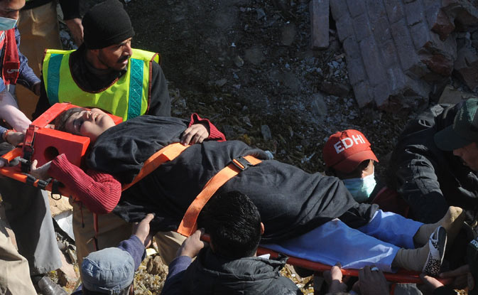 Pakistani rescue workers remove an injured woman from a collapsed factory in Lahore on February 6, 2012. ? AFP Photo