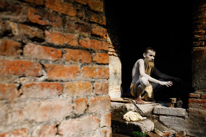 A Hindu holy man, or sadhu, sits near the fire to dry the ashes smeared on his body at his ashram in Pashupatinath Temple. ? Reuters Photo
