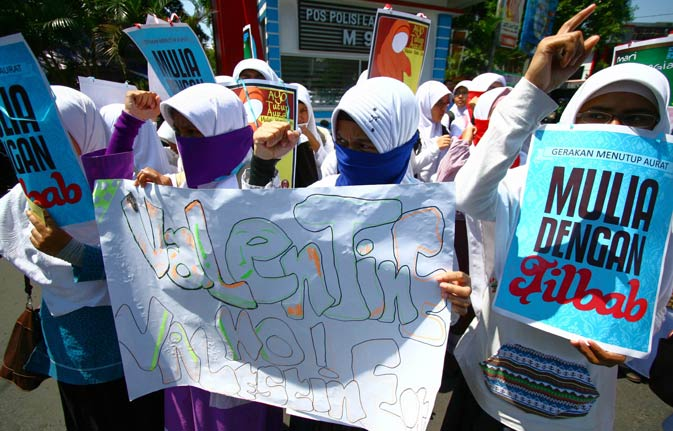 "Indonesian Muslim women hold banners that read ""Honourable by wearing veil"" and ""No Valentine's day"" during a protest against Valentine's day in Malang, East Java.  Conservative Indonesian Islamic groups denounced Valentine's Day, saying it is un-Islamic, promoting promiscuity, casual sex and consumption of alcohol. –AFP Photo."