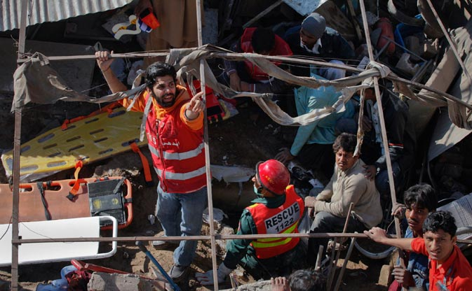 A rescue worker yells for help as they go through the aftermath of a gas explosion in Lahore on February 6, 2012. ? Reuters Photo