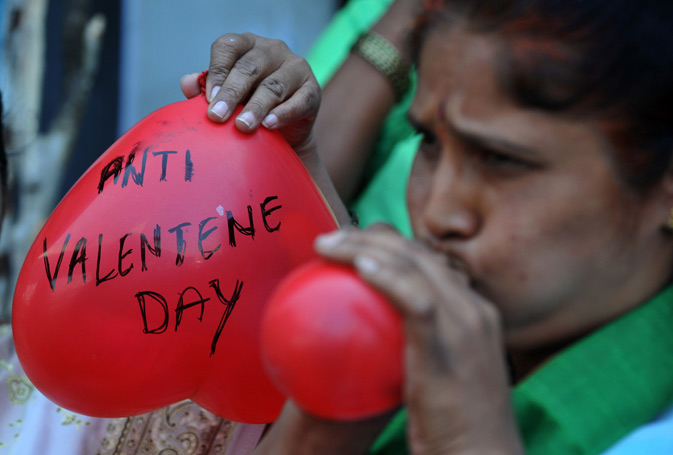 Indian women members of right-wing Bharatiya Janatha Party (BJP) blow heartshaped balloons during a protest to denounce Valentine's Day in Hyderabad. The BJP and right-wing hindu groups strongly oppose Valentine's day celebrations citing them as cultural invasion on the Hindu way of life. – AFP Photo.