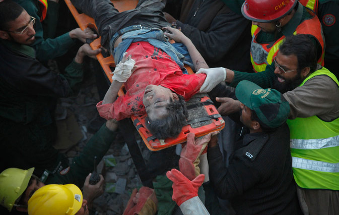 Rescue workers and residents retrieve an injured young boy from the rubble of a three-story factory which was levelled by a gas explosion in Lahore February 6, 2012. ? Reuters Photo