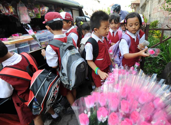 Indonesian students from a catholic school buy flowers to celebrate Valentine's Day in Denpasar on Bali island. Valentine's Day is a holiday observed on February 14 honoring one or more early Christian martyrs named Saint Valentine. – AFP Photo.