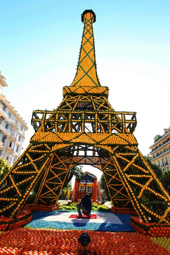 A man works on a sculpture made with oranges and lemons representing the Eiffel tower on February 16, 2012 in Menton on the French Riviera.? AFP Photo
