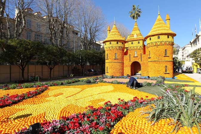 "A man works on sculptures made with oranges and lemons representing a castle on February 16, 2012 in Menton on the French Riviera, ahead of the start of the ""Fete du Citron"" (lemon carnival). ? AFP Photo"
