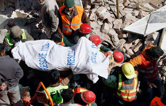 Pakistani rescue workers carry a dead body recovered from the debris of a collapsed building in Lahore, Pakistan, Tuesday, Feb. 7, 2012.  ? AP Photo