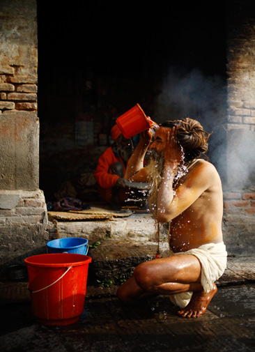 A Hindu holy man, or sadhu, takes a bath in front of his ashram at Pashupatinath Temple in Kathmandu. ? Reuters Photo