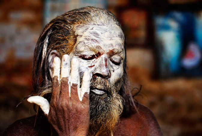 A Hindu holy man, or sadhu, applies ashes on his face at Pashupatinath Temple. ? Reuters Photo
