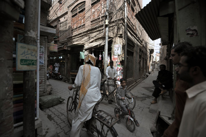 Local residents travel through narrow alleys past dilapidated buildings in the old town section of Multan on March 17, 2012 . ?AFP Photo