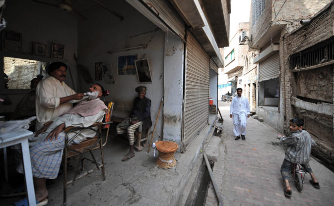Local residents go about their daily lives in the old town section of Multan on March 17, 2012. ?AFP Photo