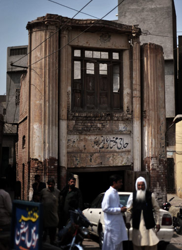 Pedestrians are seen on a street next to a dilapidated building in the old town section of Multan on March 17, 2012. ?AFP Photo