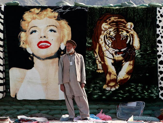 An Afghan vendor waits for customers in front of a blanket with an image of late Hollywood actress Marilyn Monroe at a bazaar in Forward Operating Base Joyce in Kunar province, eastern Afghanistan. ? Reuters Photo