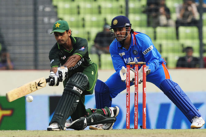 Pakistan's Mohammad Hafeez (L) plays a shot as Indian captain Mahendra Singh Dhoni (R) reacts during the one day international (ODI) Asia Cup cricket match between India and Pakistan at The Sher-e-Bangla National Cricket Stadium in Dhaka. ? AFP Photo.