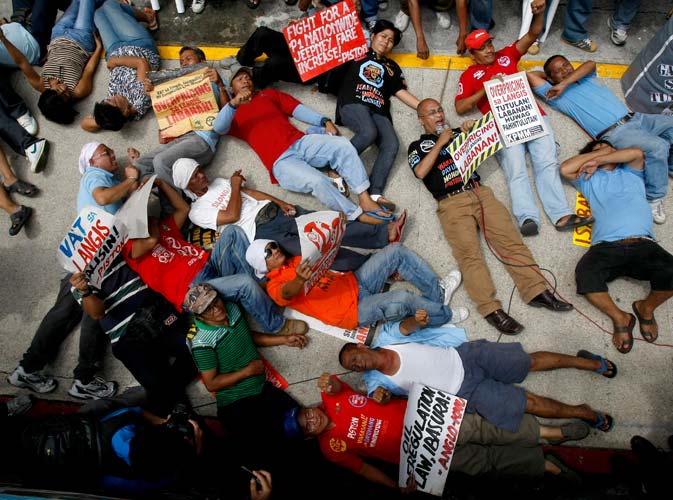 Protesters, mostly public transport drivers, shout slogans as they stage a die-in protest at the office of Shell, one of the big three oil companies in the country, during a nationwide protest against the almost-weekly rising prices of oil and other oil products at the financial district of Makati city, east of Manila, Philippines. ? AP Photo