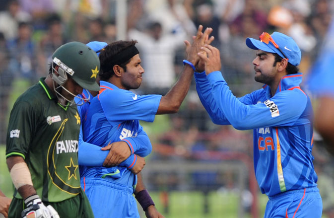 Indian cricketer Virat Kholi (R) congratulates teammate Ashok Dinda (C) after the dismissal of Pakistan's Mohammad Hafeez (L) during the one day international (ODI) Asia Cup cricket match between India and Pakistan at The Sher-e-Bangla National Cricket Stadium in Dhaka. ? AFP Photo.