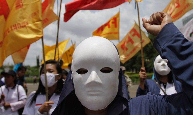 A group of labourers wearing masks protest against the government's plan to raise subsidized fuel prices, in front of the presidential palace in Jakarta. Indonesia's government is considering hiking up fuel prices, which are currently subsidised, by as much as 44 percent this year to reduce the burden of subsidies on the state's budget so that they can use these funds on roads instead, the deputy energy minister told Reuters.  ? Reuters Photo