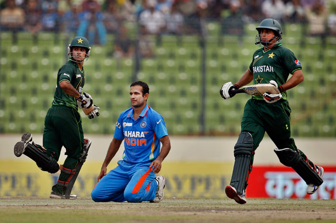 India's Irfan Pathan, center, watches as Pakistan's Mohammad Hafeez, left, and Nasir Jamshed run between the wickets during their Asia Cup cricket match in Dhaka, Bangladesh. ? AP Photo.