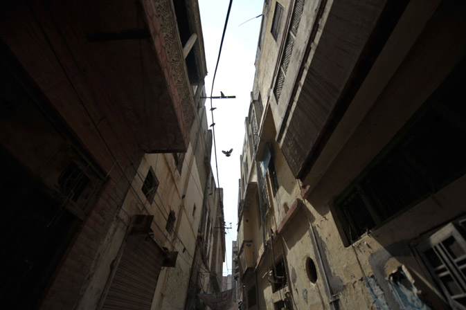 Pigeons fly above an alley lined with dilapidated buildings in the old town section of Multan . ?AFP Photo