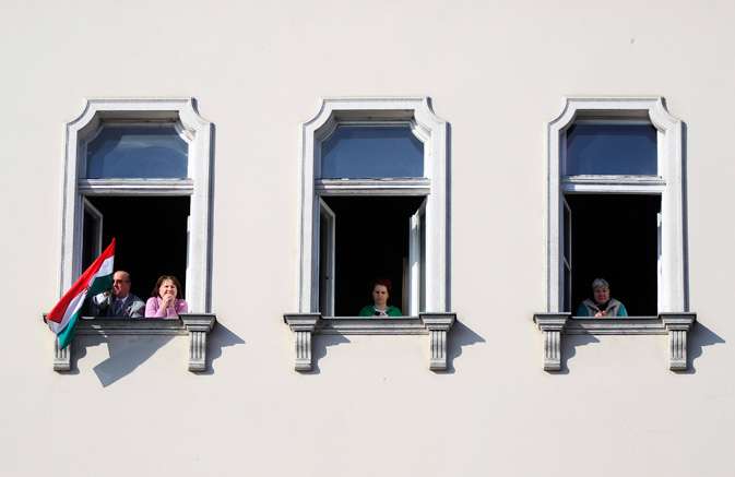 People look out their windows as they celebrate National Day, which is also the memorial day of the 1848 Hungarian Revolution against the Habsburg monarchy, in Budapest. ? Reuters Photo