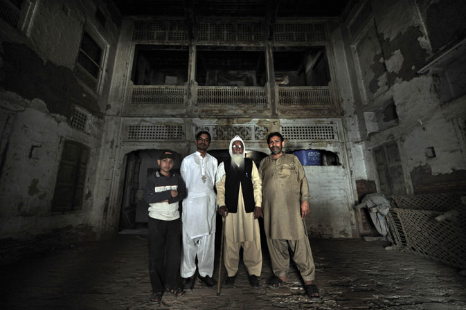 Local residents pose inside a 200-year old house undergoing ownership disputes between heirs, residents, and the local government in the old town section of Multan .