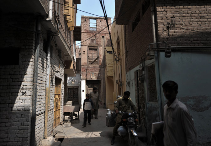 Local residents are seen in alleyways in front of a 200-year old house (C, background) undergoing ownership disputes between heirs, residents, and the local government in the old town section of Multan on March 17, 2012. ?AFP Photo