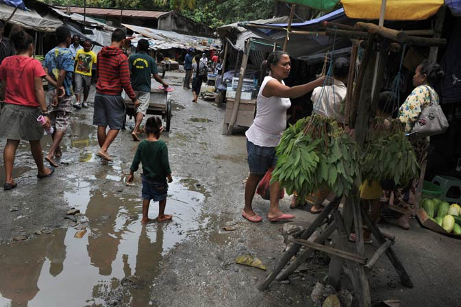 A child walks in a mud puddle at Dili's traditional market ahead of the presidential elections contested by 12 candidates. A decade after independence East Timor is restive for change, voting Saturday in the second presidential polls as a free country and hoping that an energy-fuelled bonanza will lift this tiny Southeast Asian nation out of poverty and chronic instability. ? AFP Photo