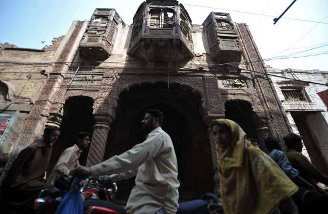 Local residents travel past a dilapidated building in the old town section of Multan on March 17, 2012. ?AFP Photo