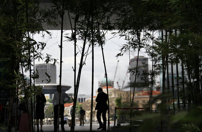 Office workers are silhouetted against the Singapore River during lunch hour in the business district of Singapore. ? AP Photo