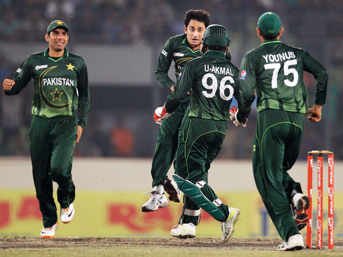 Ajmal celebrates the dismissal of Sachin Tendulkar with his team mates. -AP Photo