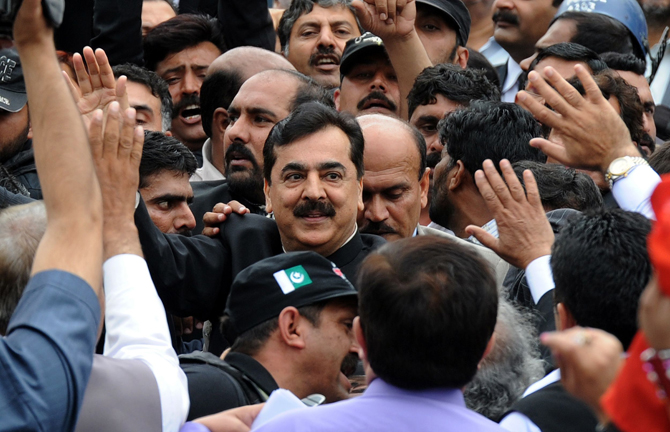 Pakistan's Prime Minister Yousuf Raza Gilani is escorted by security and supporters as he leaves the Supreme Court after a verdict in Islamabad on April 26. Pakistan's prime minister was convicted of contempt of court by the country's highest court but given only a token sentence in a case that could still see him thrown out of office. The court found Gilani guilty of contempt over his refusal to obey an order to write to the authorities in Switzerland. – Photo by AFP