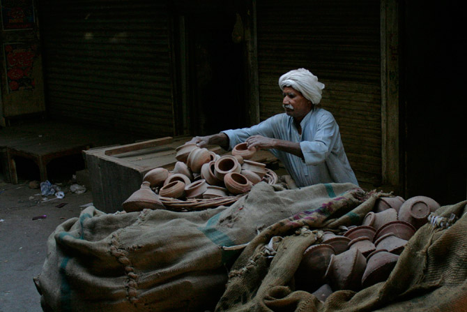A man loads clay pots on a cart for sale in a market Faisalabad. – Reuters Photo