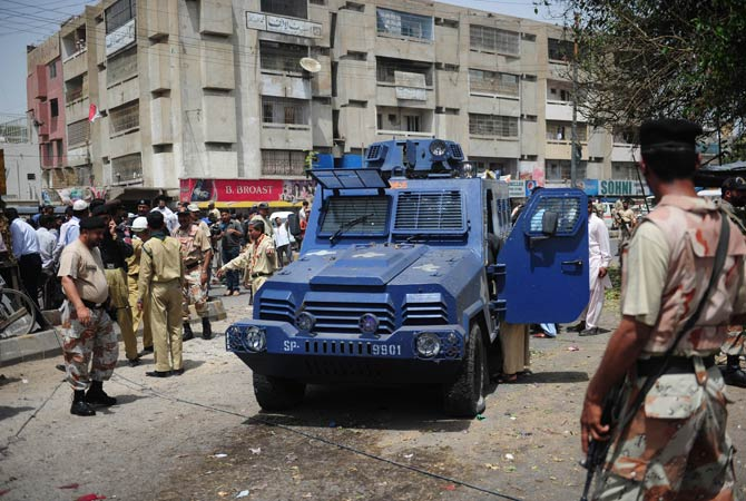 Pakistani security officials inspect a damaged armoured police vehicle at the site of a suicide bomb attack in Karachi on April 5, 2012.?Photo by AFP