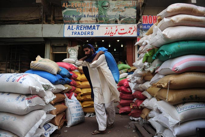 A Pakistani labourer carrying a bag of grain at a market in the port city of Karachi. – AFP Photo