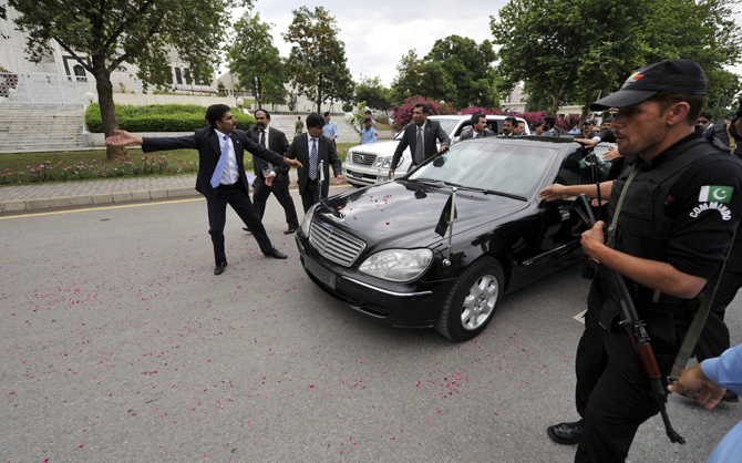 Pakistani security personnel escort Pakistan's Prime Minister Yousuf Raza Gilani's car as he leaves the Supreme Court after a verdict in Islamabad on April 26, 2012.     – Photo by AFP