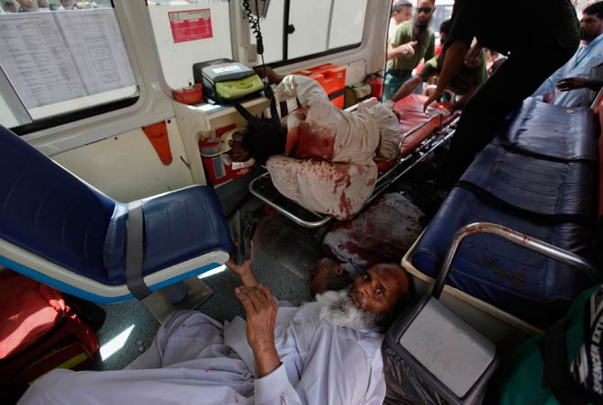 A man injured in a bomb blast lies down next to a dead victim in an ambulance, as they are brought to the Jinnah hospital from the site in Karachi April 5, 2012?Photo by Reuters.