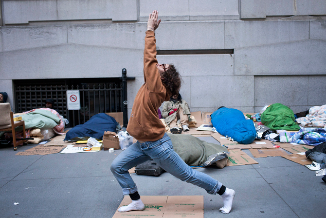 Occupy Wall Street protester Ray Leone practices yoga after sleeping at the corner of Wall Street and Nassau Street, across the street from the New York Stock Exchange, in the Financial District in New York April 12, 2012. – Reuters Photo.