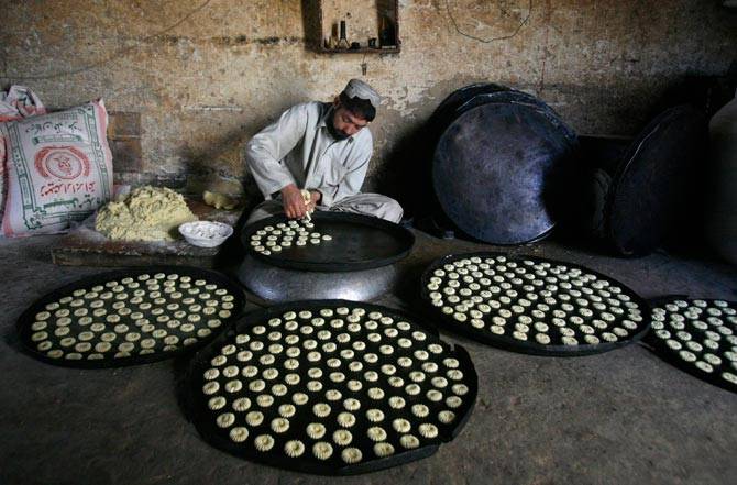 A man prepares biscuits to be backed in an oven at a workshop in Quetta. – Reuters Photo