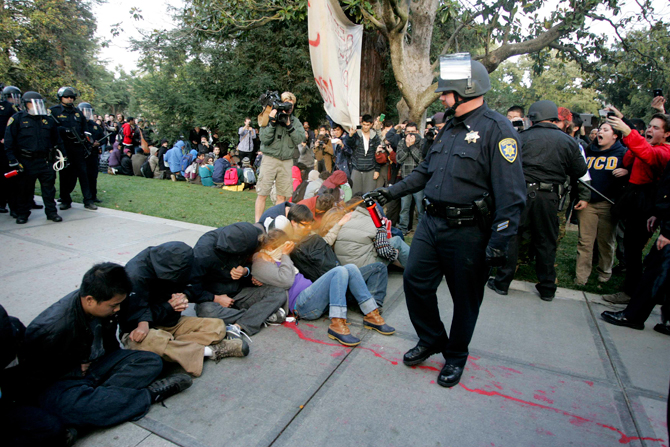 """A University of California Davis police officer pepper-sprays students during their sit-in at an """"Occupy UCD"""" demonstration in Davis, California in this November 18, 2011 file photo. University of California officials and campus police exercised poor judgment and excessive force in the pepper-spraying of students aligned with the Occupy Wall Street movement last fall, an independent review of the incident found on April 11, 2012. – Reuters Photo."""
