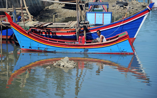 An Acehnese fisherman cleans his boat on Friday, a day of rest from fishing, in Banda Aceh on April 13, 2012, two days after powerful earthquakes hit the west coast of Sumatra.  The tsunami watch around the Indian Ocean was lifted hours after two massive earthquakes struck off Indonesia's Sumatra island on April 11, sending terrified people fleeing from the coast. ? Photo by AFP