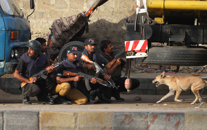Police commandos take cover during a crackdown operation against criminals. – Photo by AP