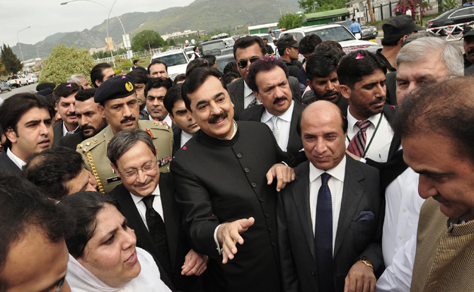 Pakistani Prime Minister Yousuf Raza Gilani, center, makes his way to the Supreme Court for a hearing in Islamabad, Pakistan, Thursday, April 26, 2012.  – Photo by AP